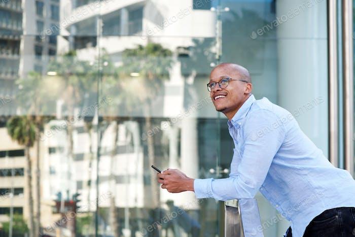 afrikanische Geschäftsmann stehend außerhalb mit Handy
