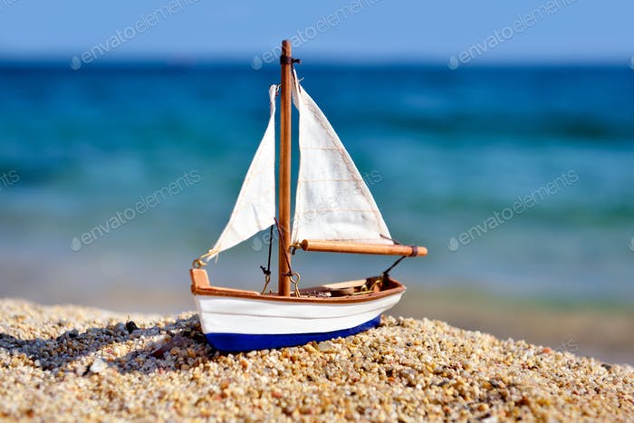 Miniature toy sailboat on the beach