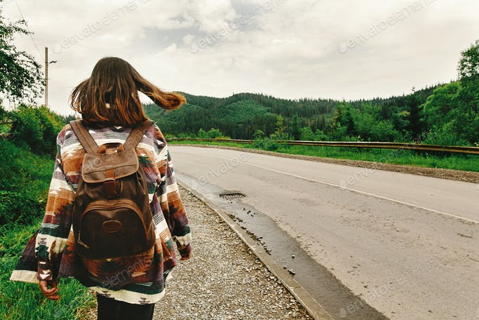 Woman traveler with backpack walking down the road in mountains