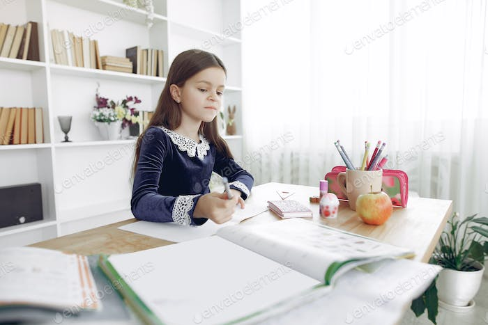 Little girl sitting on a table with books