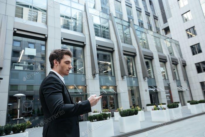 Man in big center using smartphone
