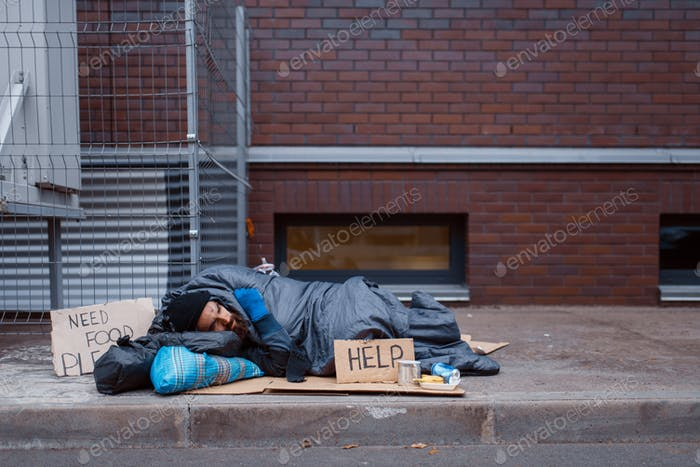 Dirty homeless with help sign lies on city street
