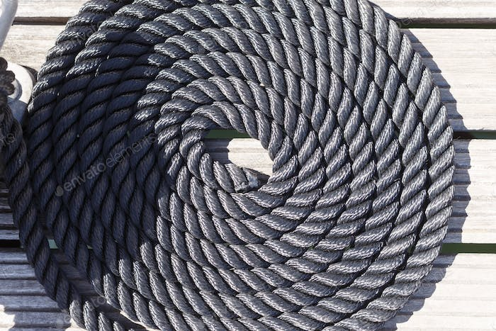 Close-up of a mooring rope on a wooden pier/ Nautical mooring ro