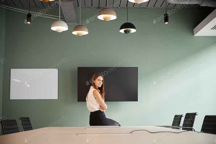 Portrait Of Young Businesswoman Sitting On Boardroom Table