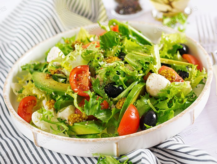Fresh salad with avocado, tomato, olives and mozzarella  in a  bowl.  Fitness food. Vegetarian meal.