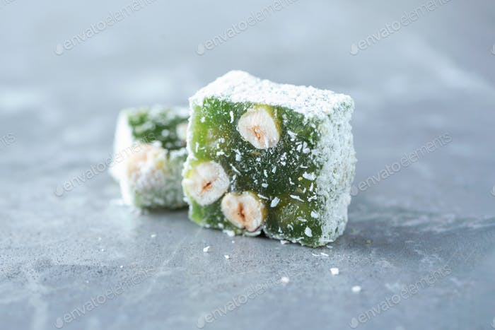 Turkish delight - lokum or rahat lokum with hazelnuts on grey background. Traditional eastern