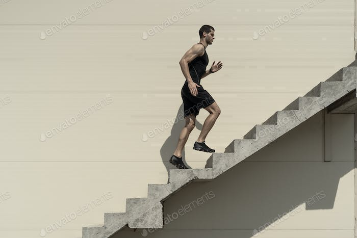 Ambitions concept with sportsman climbing stairs.