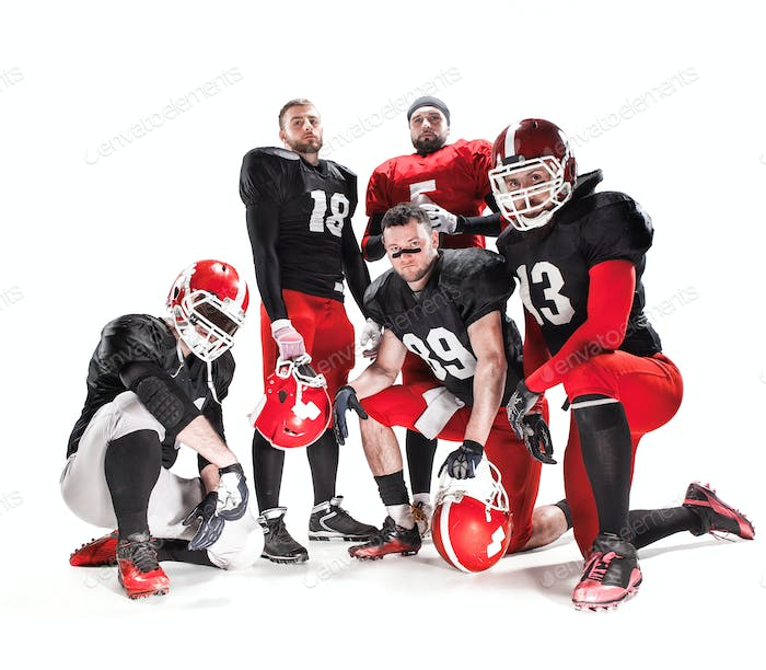 The five american football players posing with ball on white background