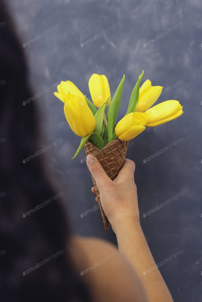 Yellow tulips in ice cream cone in girls hand on cement backgrou