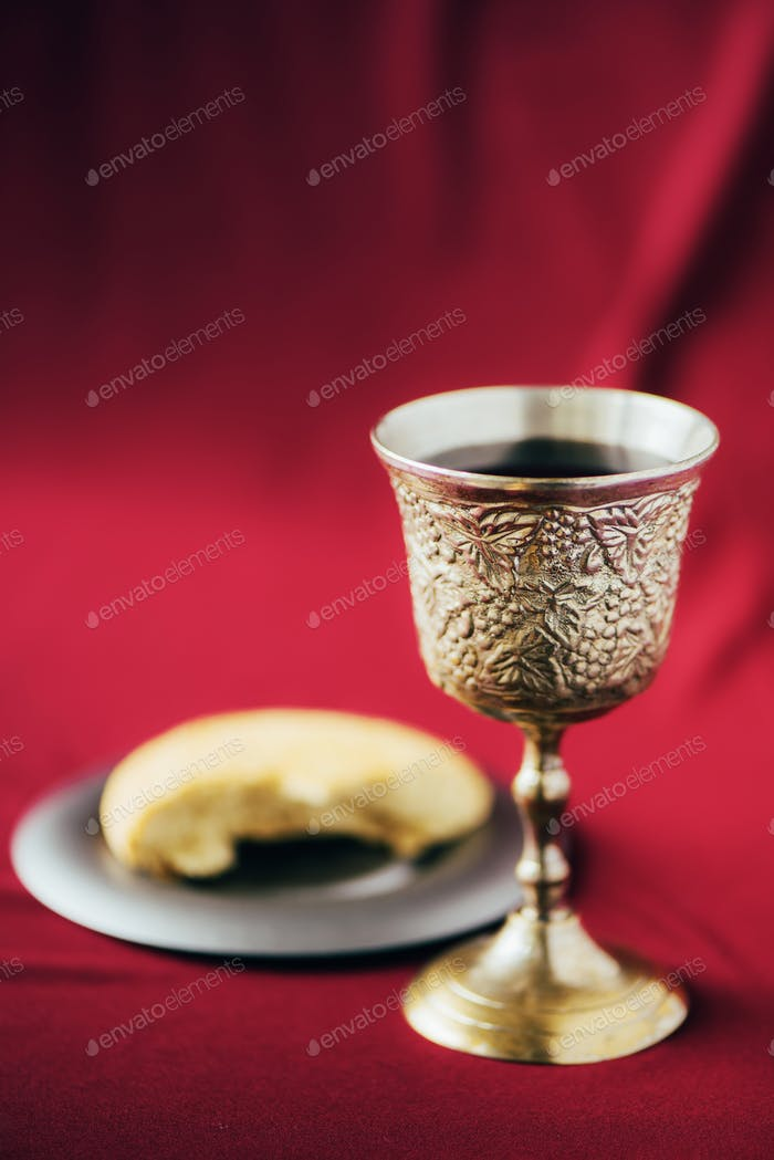 Unleavened bread, chalice of wine, silver kiddush wine cup on red background. Communion still life