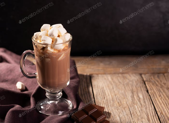 Hot chocolate with cinnamon and marshmallow on wooden background