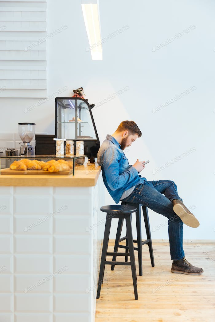 Man using smartphone in cafe