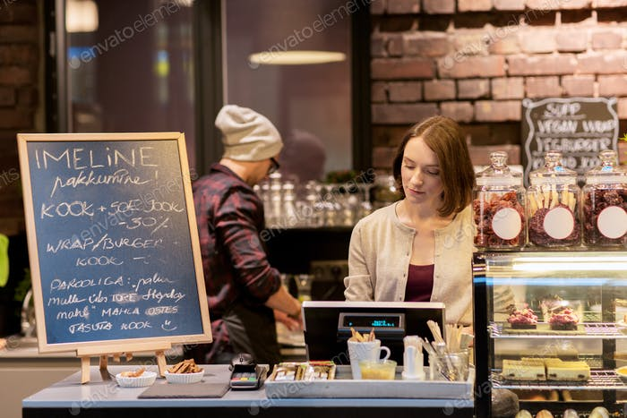 woman bartender at cafe or coffee shop cashbox