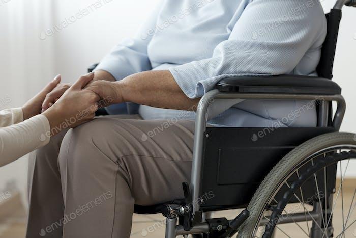 Nahaufnahme einer Person, die eine gelähmte ältere Frau in einem