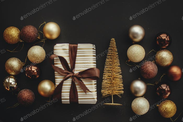 Christmas gold tree and  gift box with glitter baubles on stylish black background