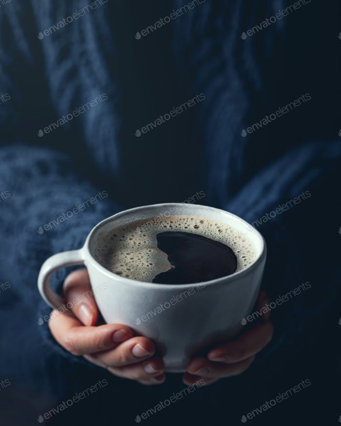 Woman hands holding a cup of hot coffee