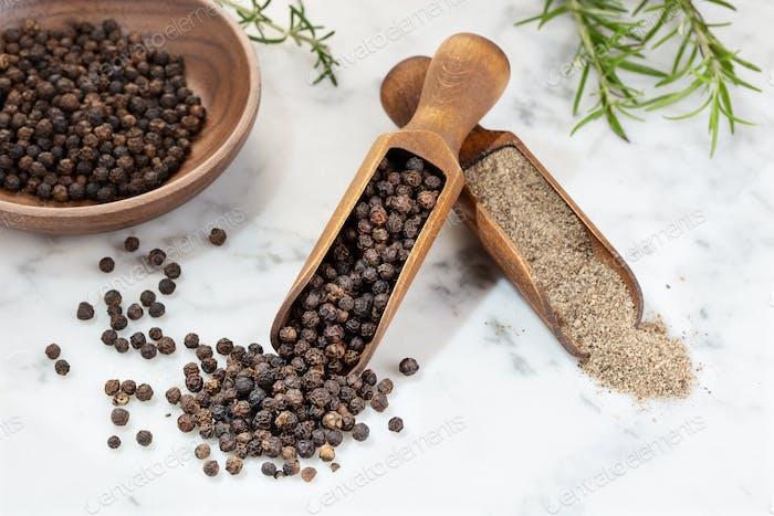 Schwarzer Pfeffer Samen und gemahlener Pfeffer auf Marmortisch.