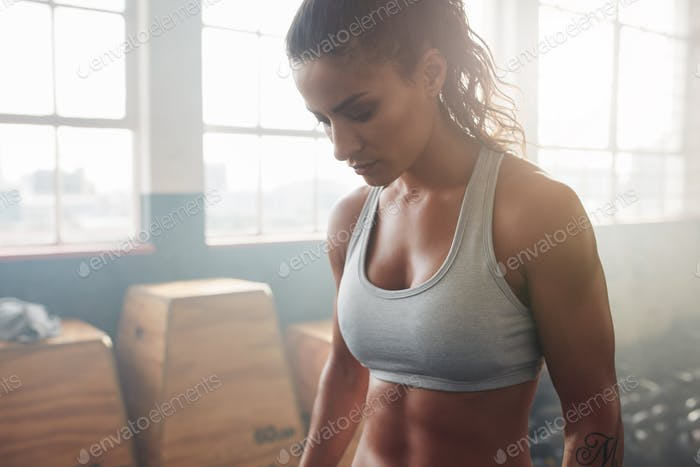 Muscular woman standing in the gym