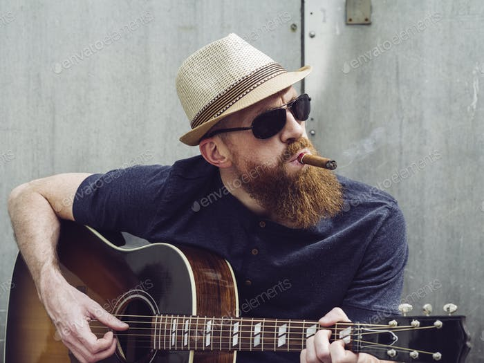 Bearded man playing acoustic guitar and smoking cigar