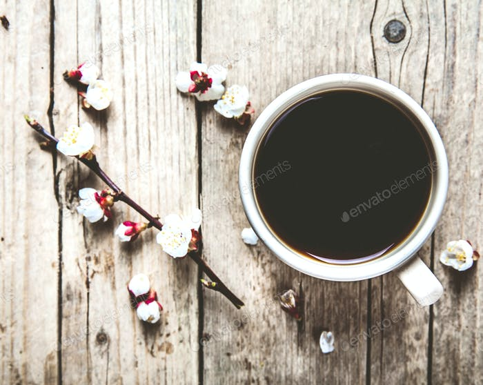 Cherry blossoms on a wooden background with a cup of coffee