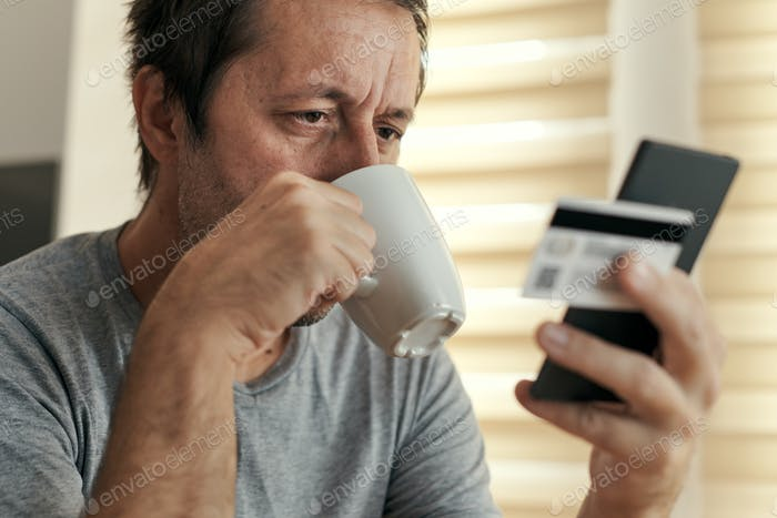 Man shopping online from home with mobile phone and credit card