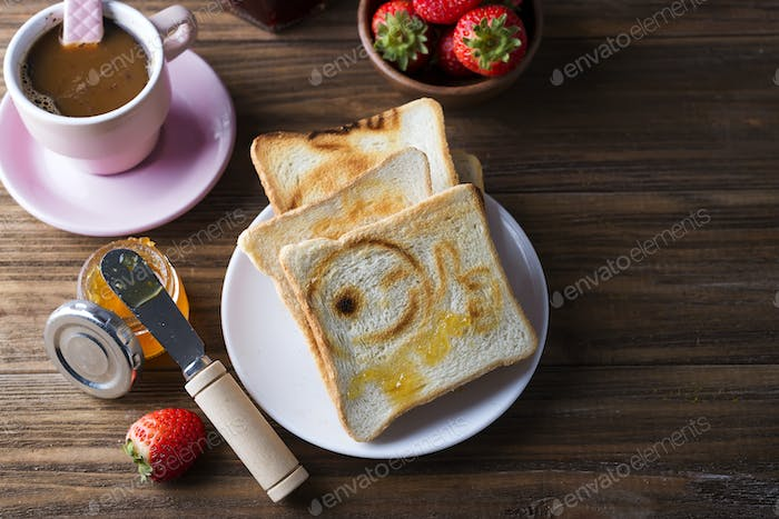 Breakfast with coffee, toasts, strawberry and jam