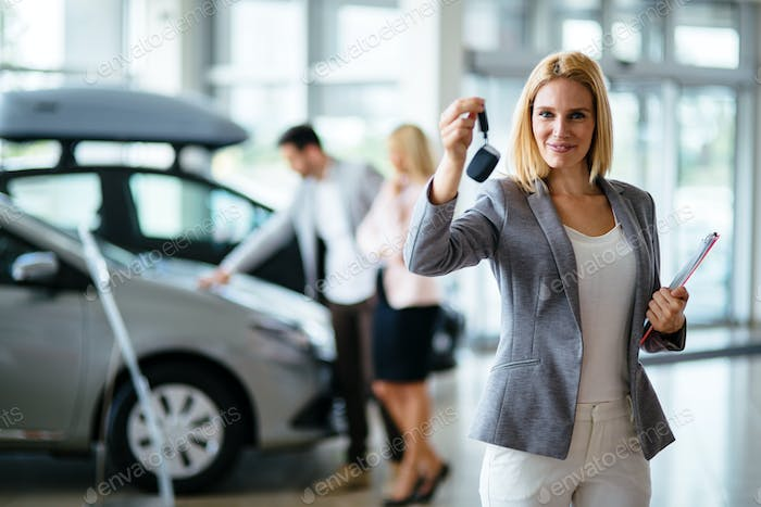 Portrait of beautiful saleswoman standing inside vehicle showroom