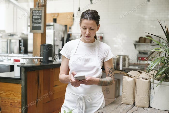 Woman wearing a white apron standing in a kitchen, using a mobile phone.