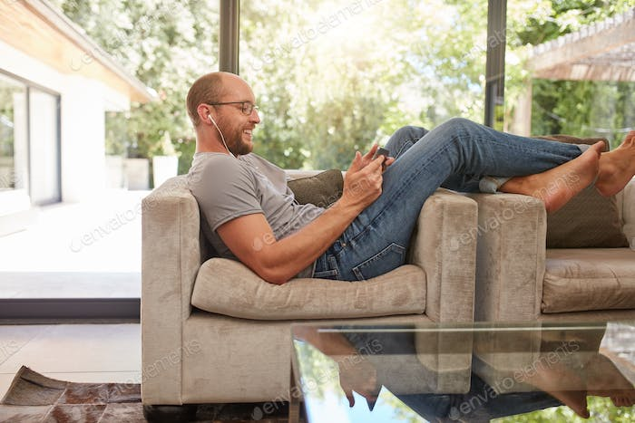 Man relaxing on sofa using tablet PC