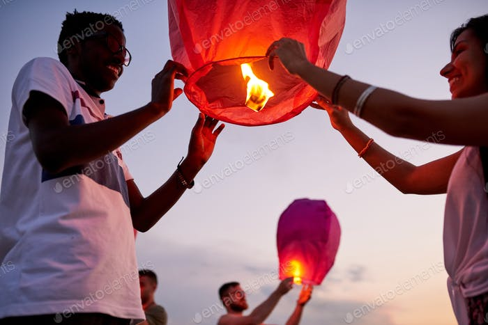 Happy friends launching sky lanterns