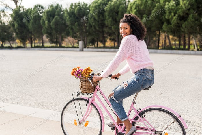 Black young woman riding a vintage bicycle