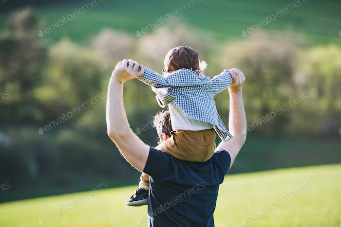 A father giving toddler son piggyback ride outside in spring nature.