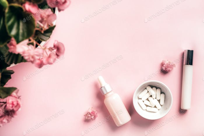 Cosmetic bottles and white capsules with begonia flowers