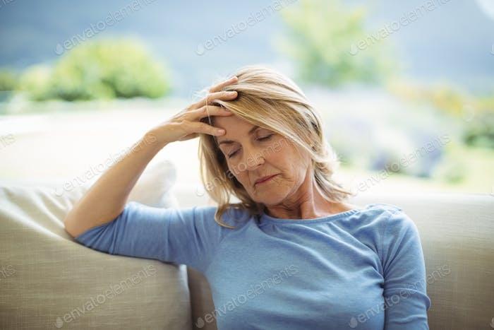 Tense senior woman sitting on sofa in living room