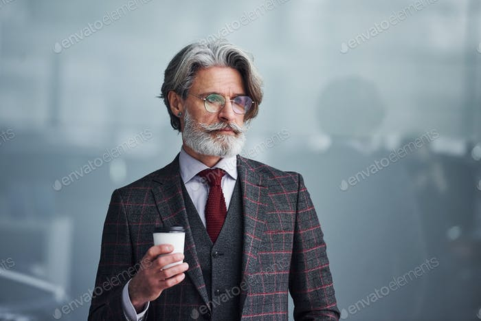 Senior businessman in suit and tie with gray hair and beard standing with cup in hand