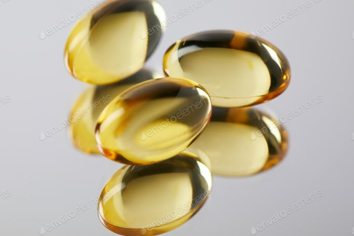heap of omega fish hat supplement capsules on reflective surface