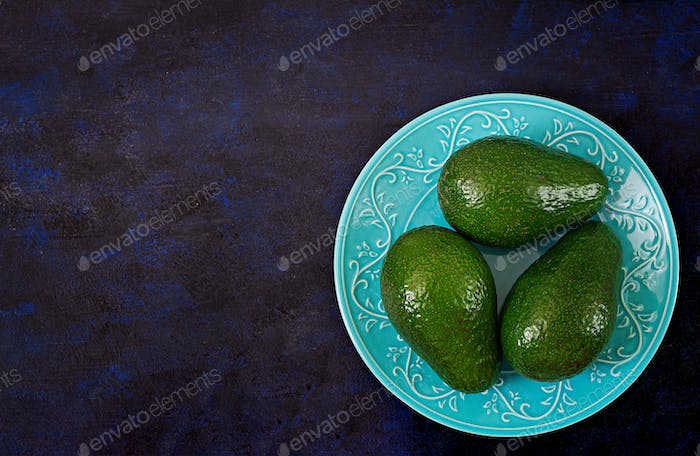 Three ripe avocados on a dark table. Healthy food concept. Top view
