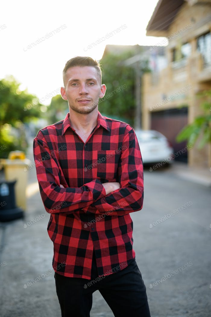 Young man wearing red checkered shirt in the streets outdoors