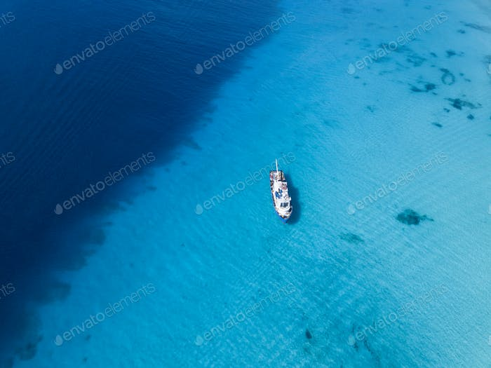 Aerial view of ship floating over crystal clear waters of Grand