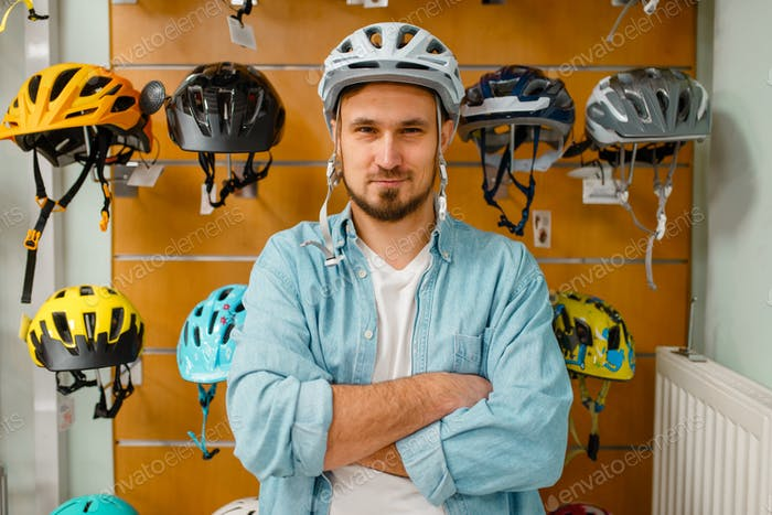 Man trying on cycling helmet in sports shop