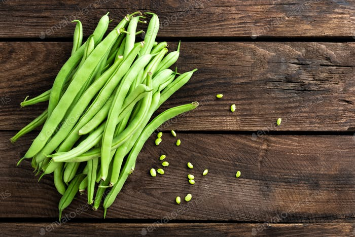 Fresh green beans on dark wooden rustic background top view copy space flat lay