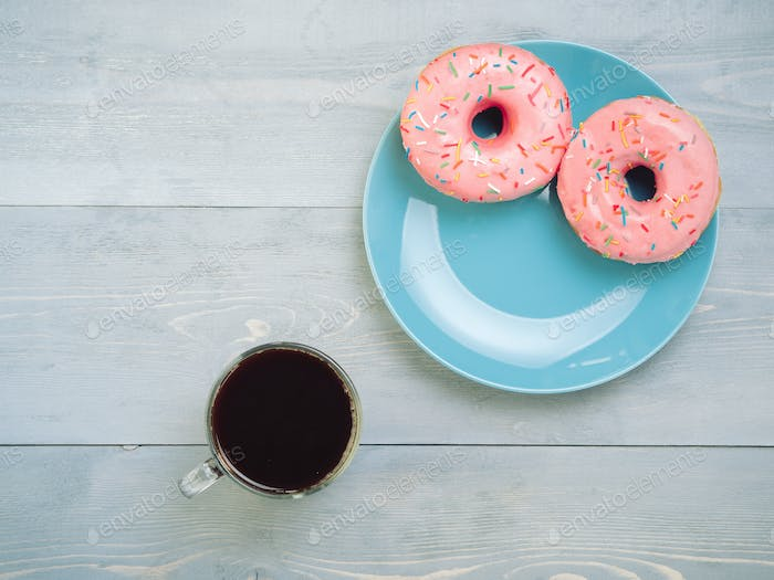 pink donuts and coffee on gray wooden background