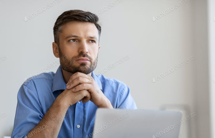 Portrait Of Pensive Businessman Sitting At Workplace With Laptop And Looking Away