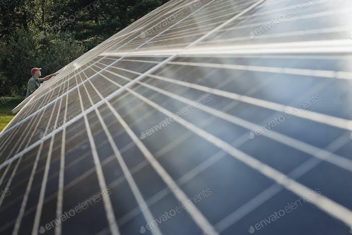 Ein Mann, der die Oberfläche eines großen geneigten Solarpanels inspiziert.
