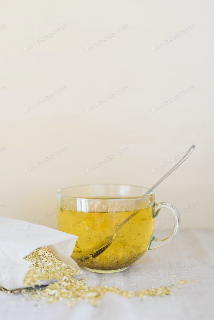 herbal tea with dried chamomile flowers into glass cup