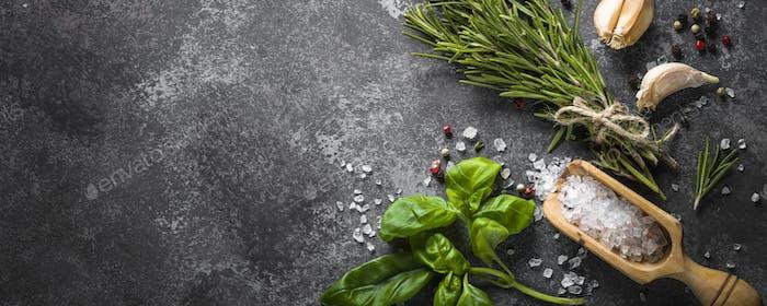 Gewürze und Kräuter über schwarzen Steintisch