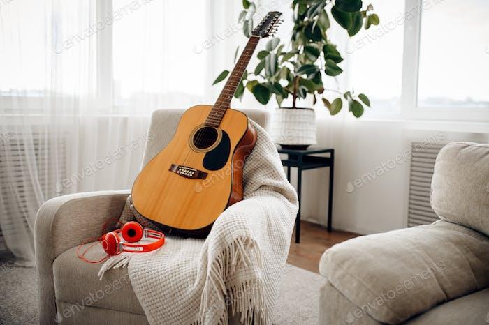 Gitarre und Kopfhörer auf weißem Sessel, niemand