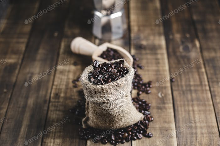 coffee beans in bag wooden scoop and moka pot with wood background