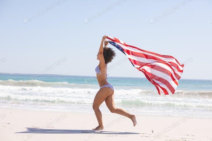 Seitenansicht von African American Frau im Bikini mit amerikanischer Flagge läuft am Strand
