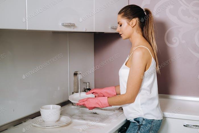 ama de casa chica en guantes de color rosa lava platos a mano en el fregadero con detergente. La chica limpia el